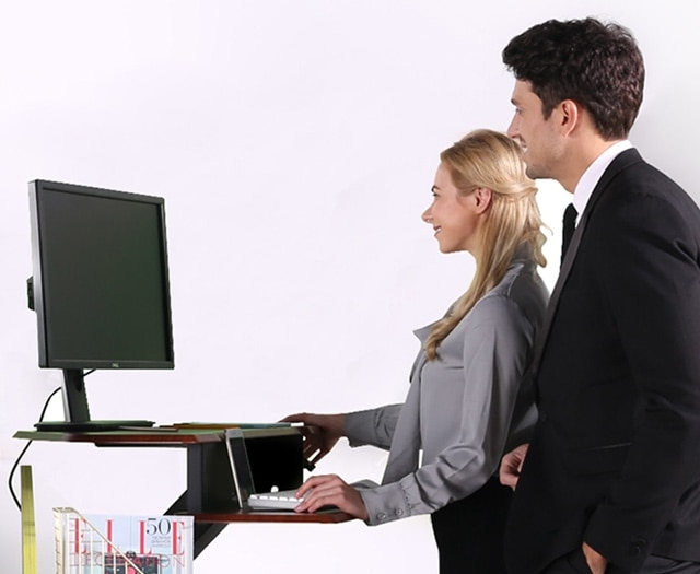 Two coworkers using the iMovR+Eureka 28″ Z-Lift Corner Standing Desk Converter.