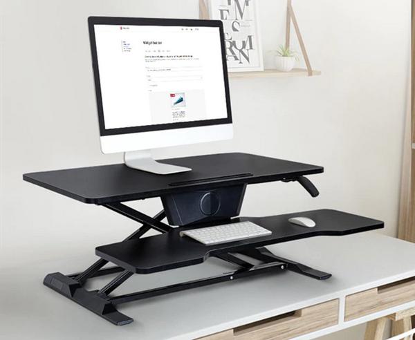 iMovR+Eureka 32″ X-Lift Sit-Stand Desk Converter on a wooden desk.