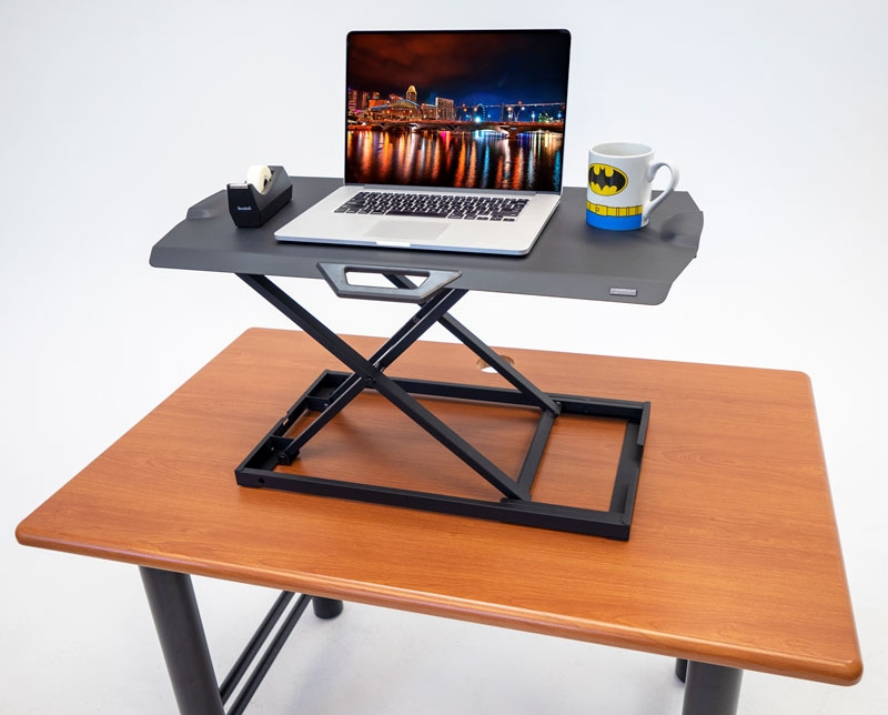 iMovR+Eureka Ultra-Slim Portable Sit-Stand Desk Converter in a raised position on a wooden desk.